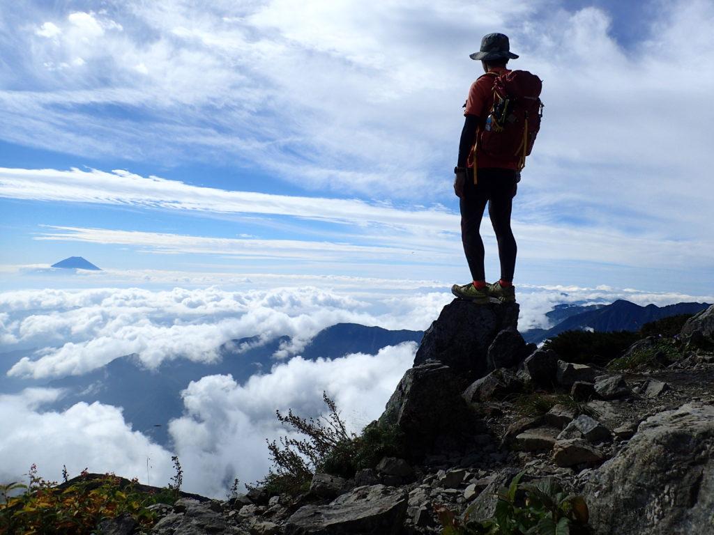 日本百名山である北岳山頂に立つ背中にモンベルの登山用ザックであるバーサライトパック