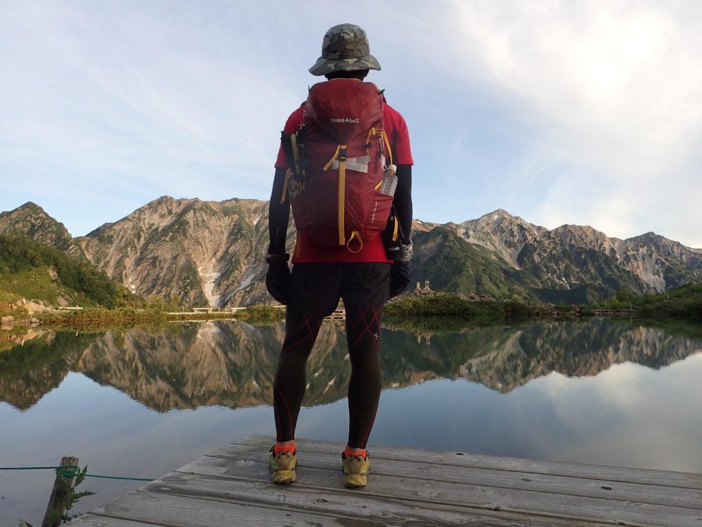 白馬三山と八方池を眺める背中にモンベルの登山用ザックであるバーサライトパック