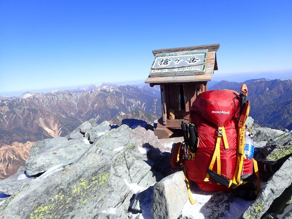 槍ヶ岳山頂の祠とモンベルの登山用ザックであるバーサライトパックの記念撮影