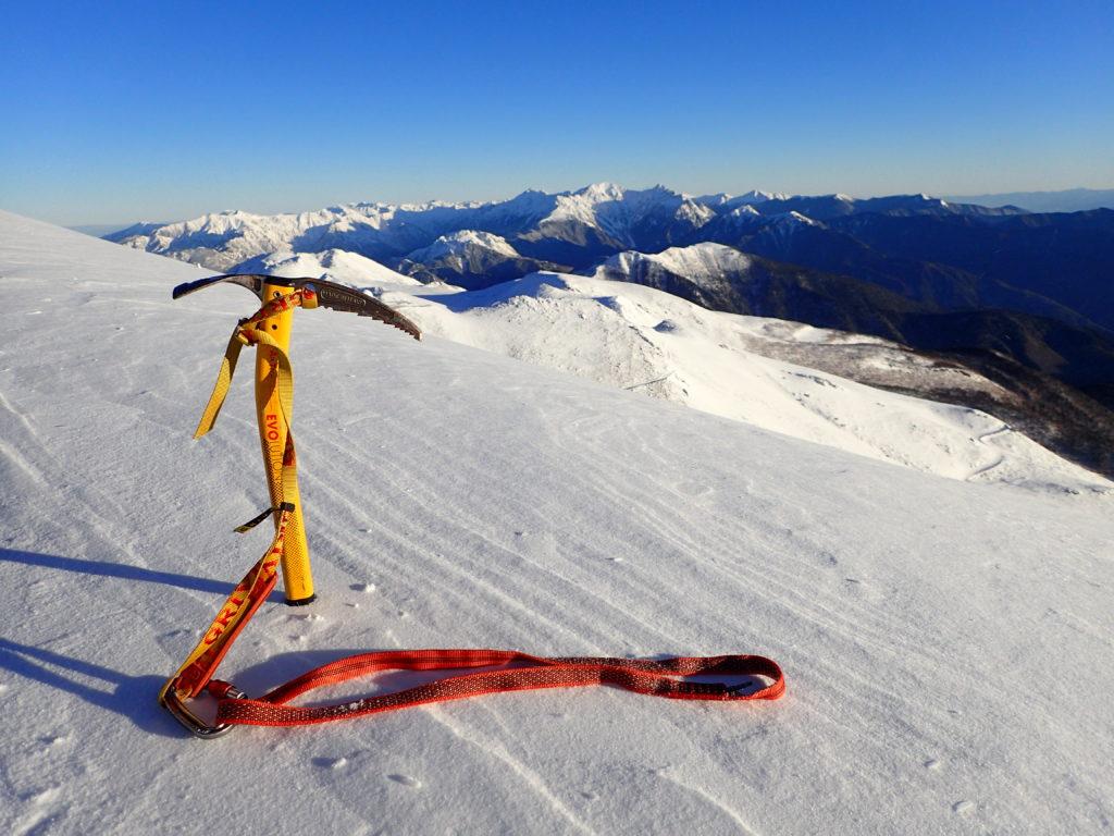冬の乗鞍岳稜線で槍ヶ岳と穂高岳をバックにグリベルのピッケルであるエアーテックエヴォリューションの記念撮影