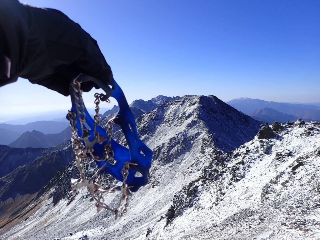 秋も深まる10月下旬の槍ヶ岳山頂で下山に向けてモンベルの軽アイゼンであるチェーンスパイクを装着準備