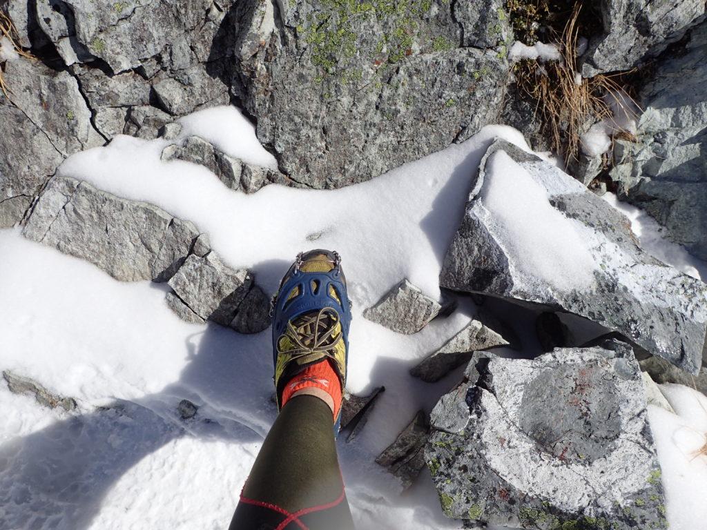 秋も深まる10月の槍ヶ岳山頂でモンベルの軽アイゼンであるチェーンスパイクをトレランシューズに装着