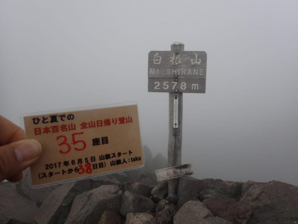 ひと夏での日本百名山全山日帰り登山で登った日光白根山の山頂で自作の登頂カードで記念写真