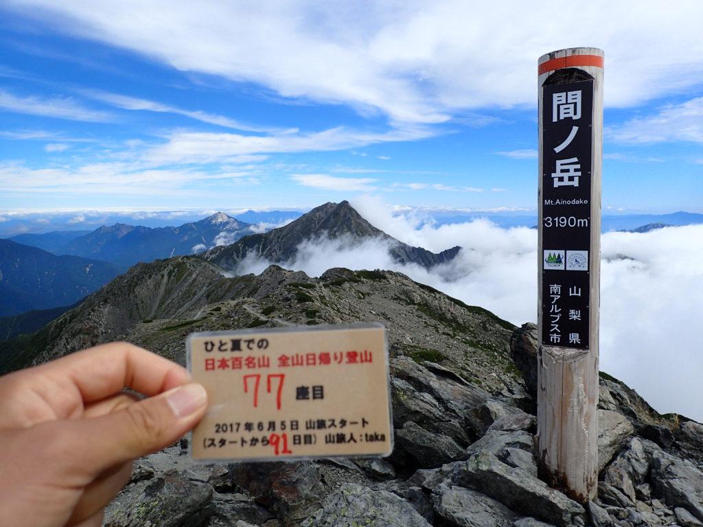 ひと夏での日本百名山全山日帰り登山で登った間ノ岳の山頂で自作の登頂カードで記念写真