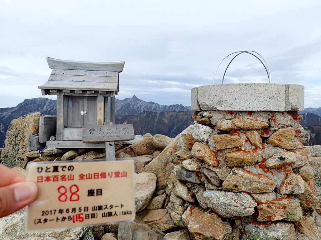 ひと夏での日本百名山全山日帰り登山で登った常念岳の山頂で自作の登頂カードで記念写真