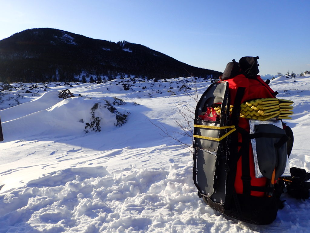冬の北八ヶ岳の坪庭でザックに外付けされたMSRのスノーシューであるライトニングアッセントの記念撮影