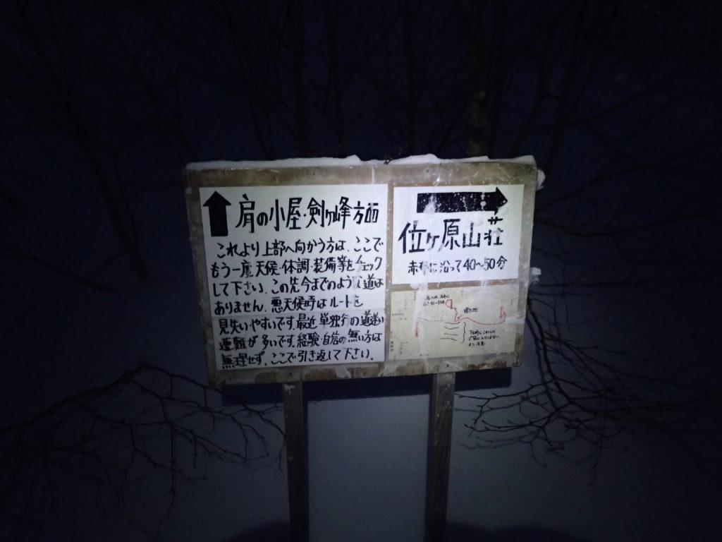 まだ暗い午前6時の冬の乗鞍岳バックカントリーツアーコース終点の看板をブラックダイヤモンドの登山用ヘッドライトであるストームの灯りで照らす