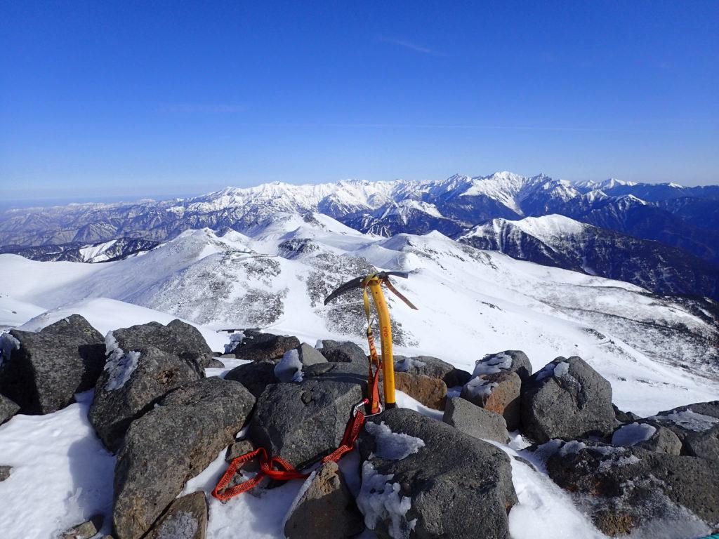 冬の乗鞍岳剣ヶ峰山頂で槍ヶ岳や穂高岳をバックにグリベルのピッケルであるエアーテックエヴォリューションの記念撮影