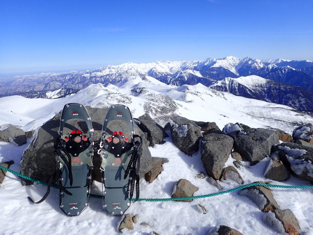 冬の乗鞍岳剣ヶ峰山頂で槍ヶ岳、穂高岳を背景にMSRのスノーシューであるライトニングアッセントの記念撮影