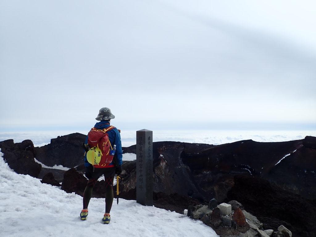 日本最高峰富士山剣ヶ峰山頂でモンベルの登山用レインウェアであるトレントフライヤーを着て記念写真を撮影