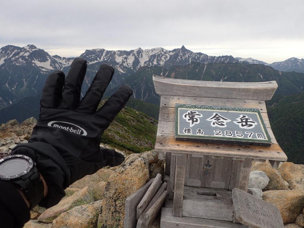 常念岳山頂で槍ヶ岳をバックにモンベルの登山用グローブであるサンダーパスグローブの記念写真を撮影