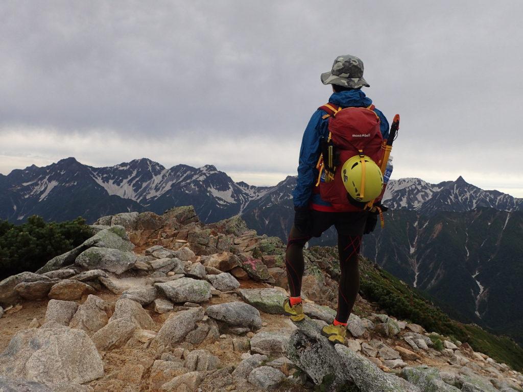 梅雨空の常念岳山頂でモンベルの登山用レインウェアであるトレントフライヤーを着て槍ヶ岳と穂高岳の稜線をバックに記念写真を撮影