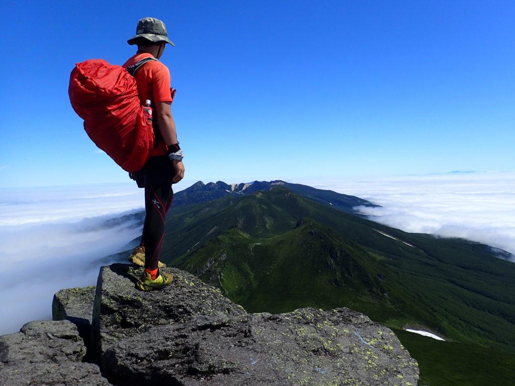 北海道の羅臼岳山頂でザックカバーをかけたザックを背負って記念撮影