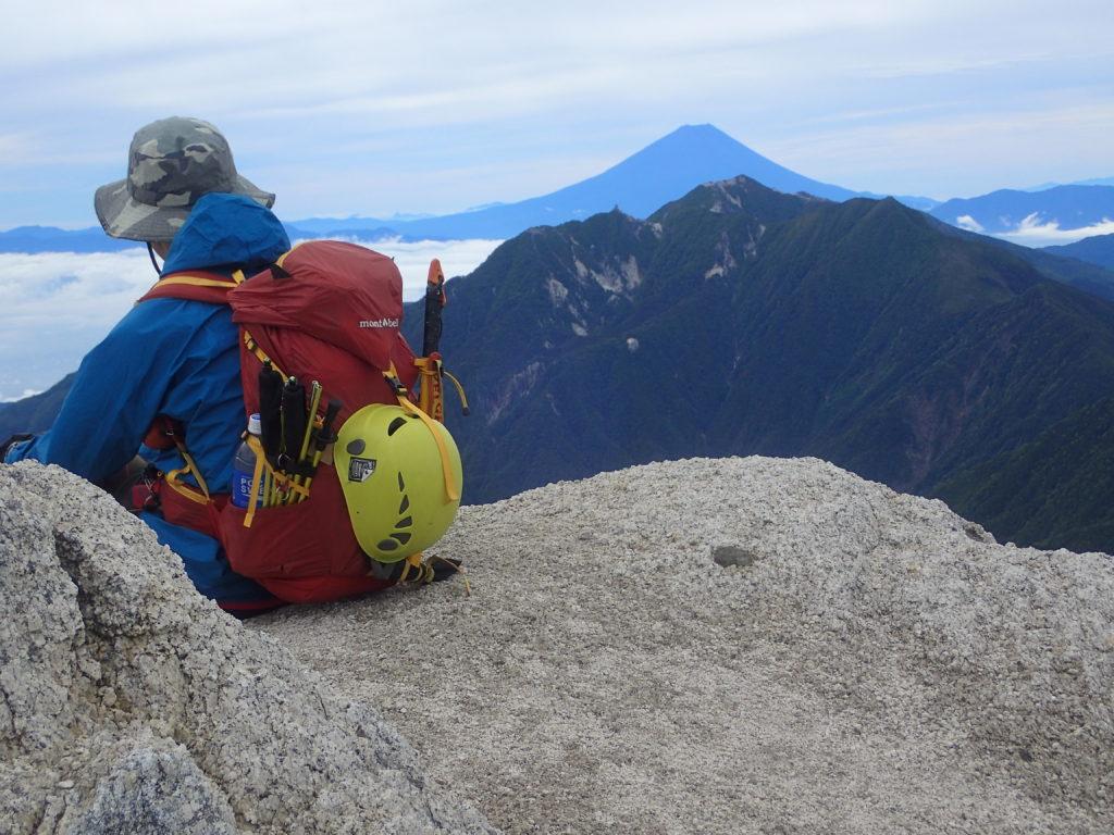 甲斐駒ヶ岳山頂で鳳凰三山の向こうに富士山を眺める背中にモンベルの登山用ザックであるバーサライトパック30