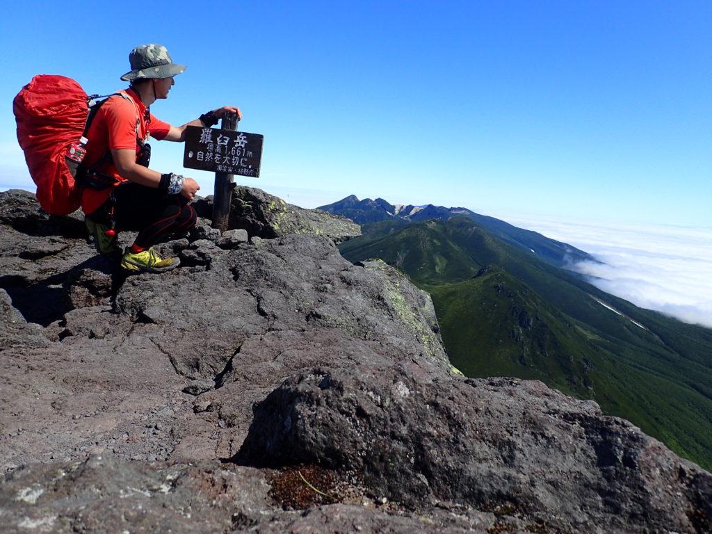 北海道の羅臼岳山頂でゴアッテックス製の登山用の帽子を被って記念撮影
