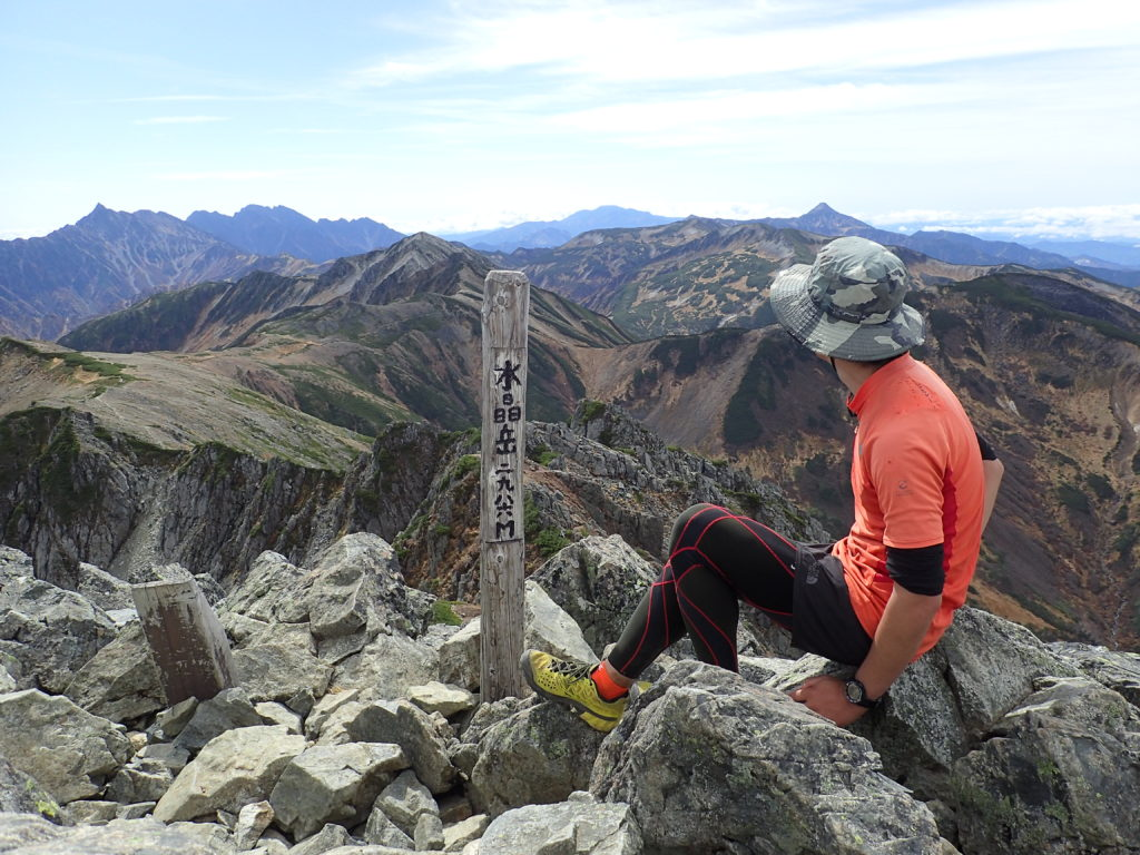 北アルプスの水晶岳山頂で登山用の帽子の記念撮影