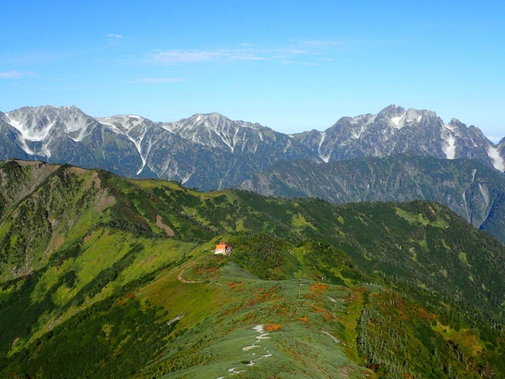 北アルプス爺ヶ種の種池山荘のオレンジ色の屋根と背景に剱岳